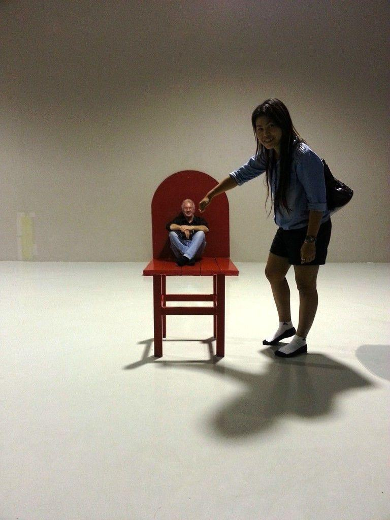 A chair painted on the floor and wall to mke it look as if the person sitting has been shrunk