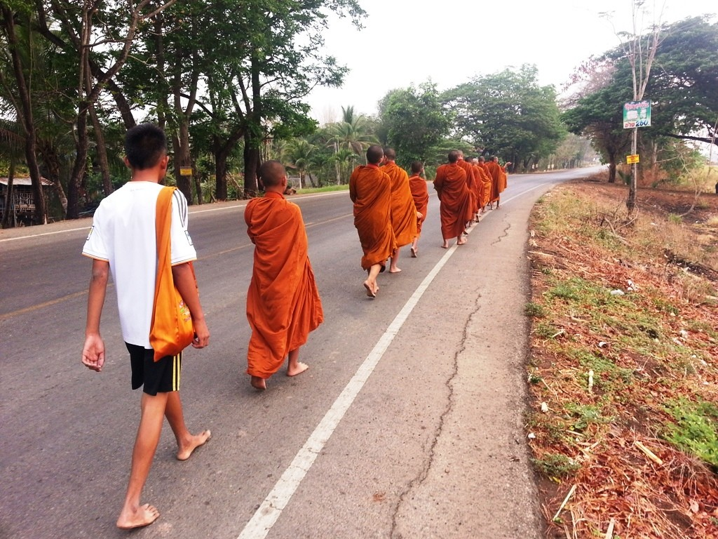 Several Buddhist Monks walking beside the road returning to monastery