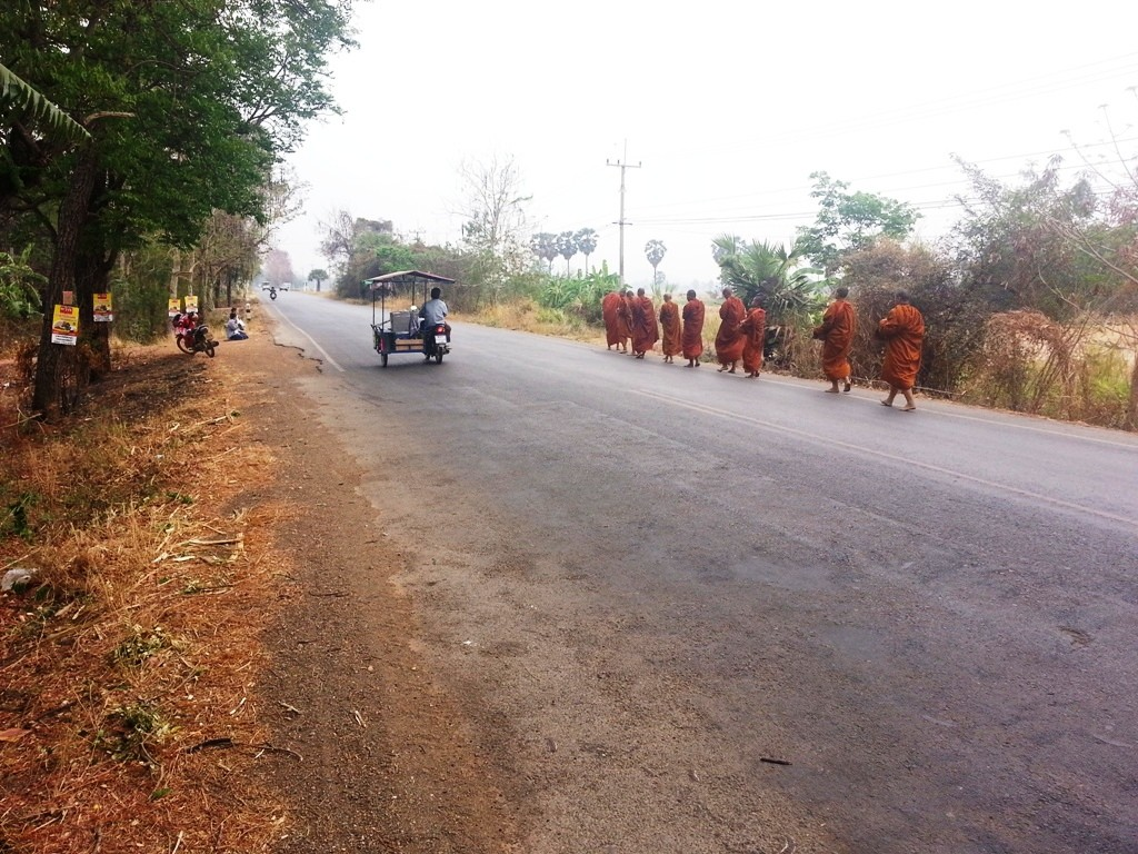 Ladies in the distance sitting beside the road making Pindapata obvious