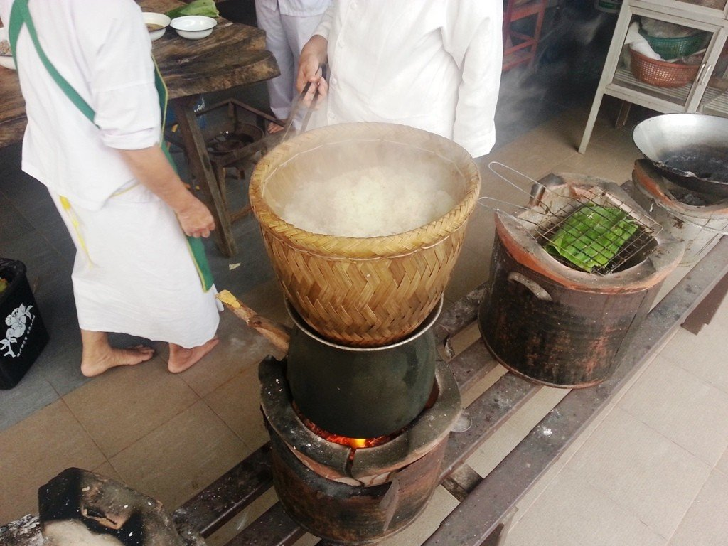 Rice being steamed on a traditional outdoor wood fired bucket BBQ.