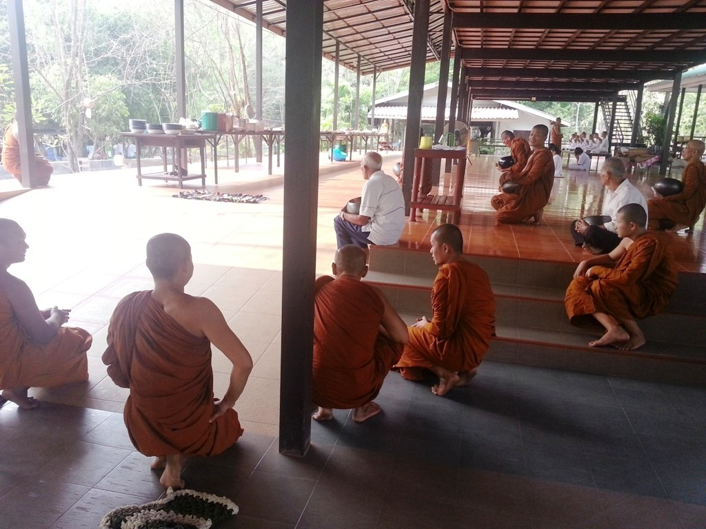 The monks all kneel in respect as Phra Ajahn arrives for breakfast