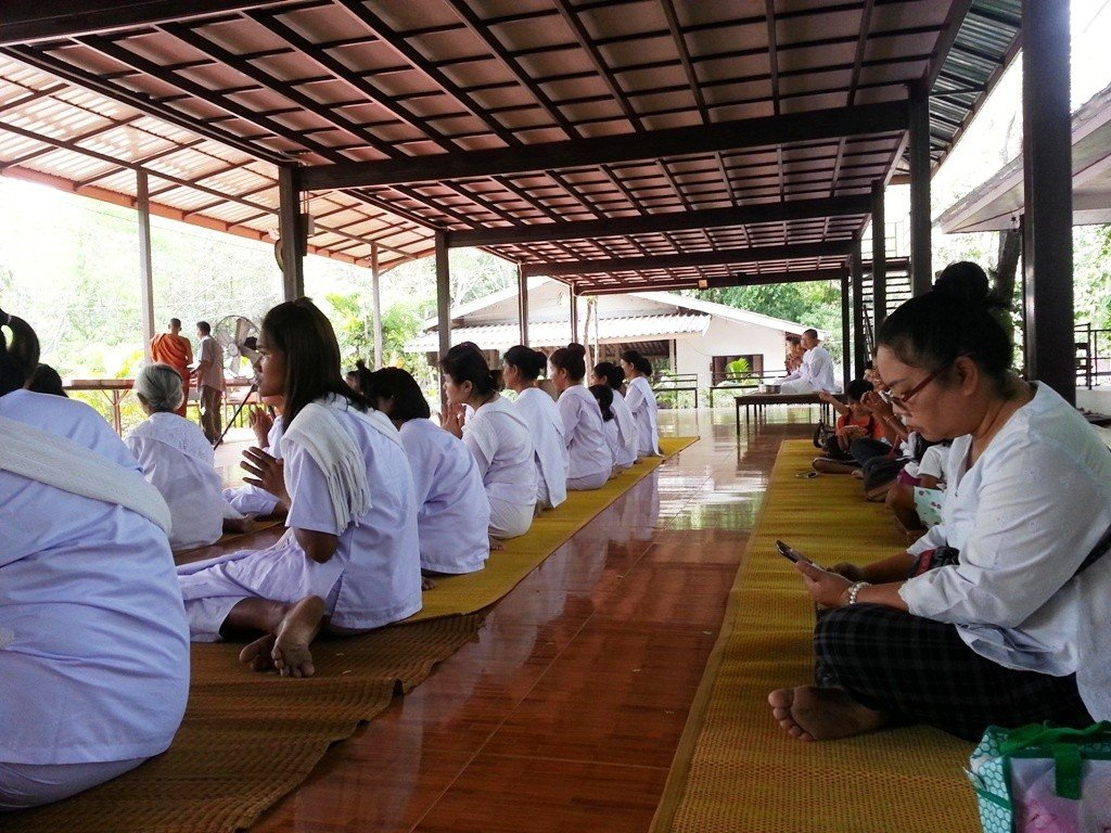 Ladies sitting with hands together as the monks select their food