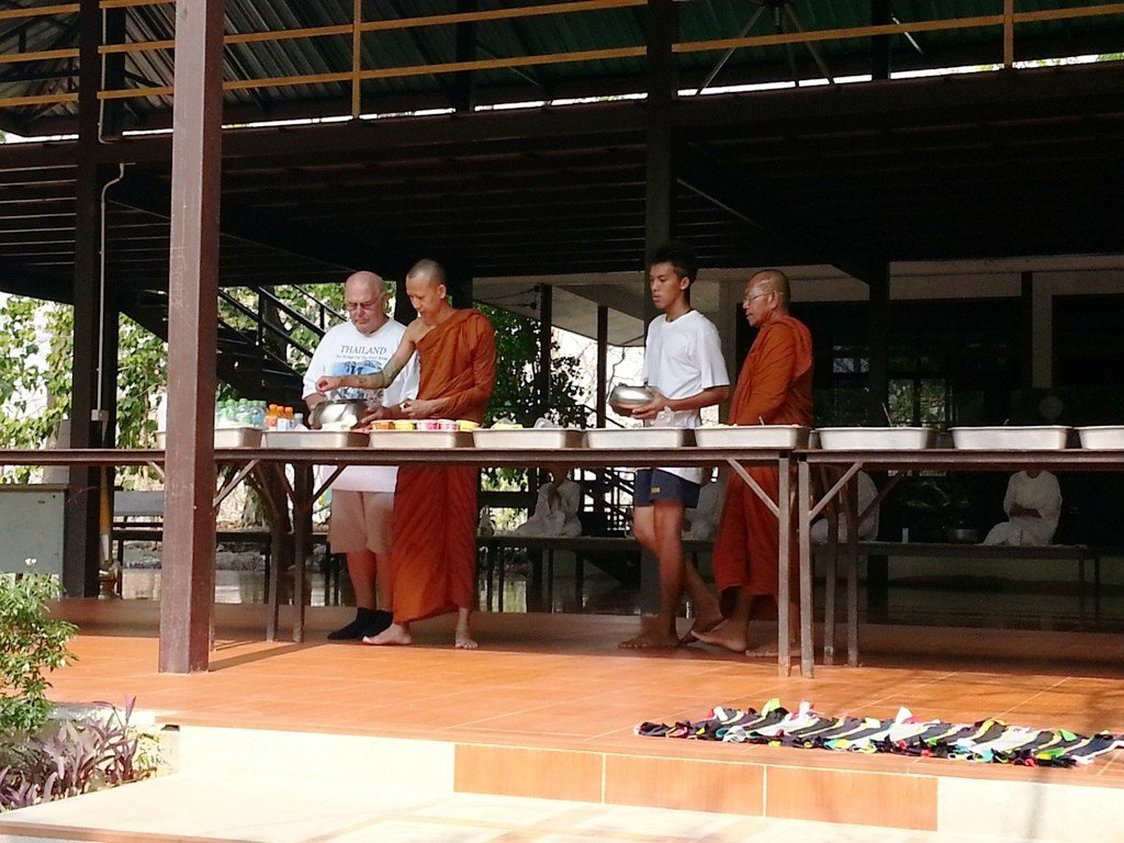 A western visitor carries the bowl for a Buddhist Monk in a Thai Monastary