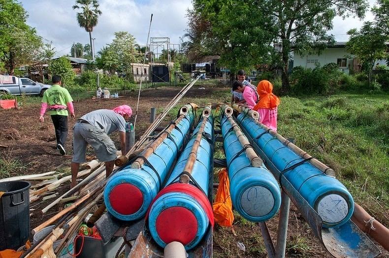 Large rockets made from blue plastic pipe being prepared for the festival