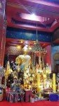 Golden Buddha image with candles and gifts inside Wat Tub Berk