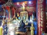 A statue of a golden Buddha and a black monk inside Wat Tub Berk